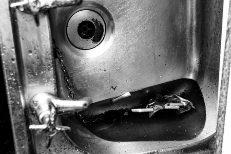 discarded: Discarded metal sink gathers rain water and cigarette butts in black and white