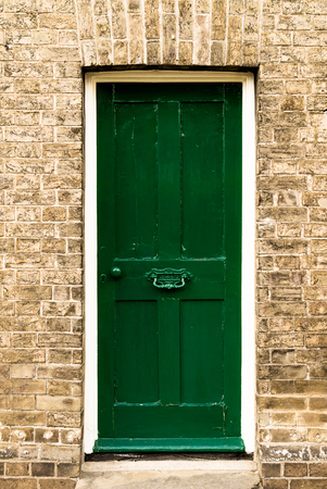 Single green painted wooden residential front door set in a traditional brickwork exterior