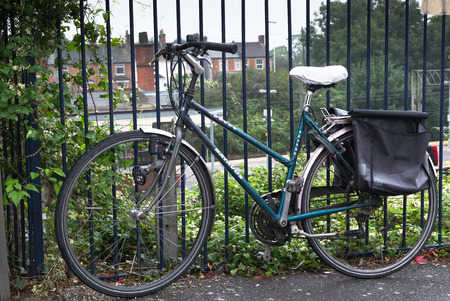 saddlebag: 13 Aug - Green classical bicycle with saddle bags attached to railings at Witham train station in August 2015