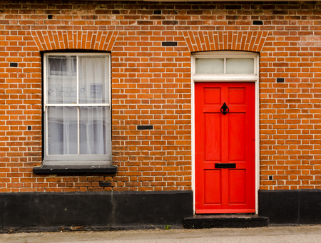 Single red painted wooden residential front door set in a traditional brickwork exterior with a window Stockfoto