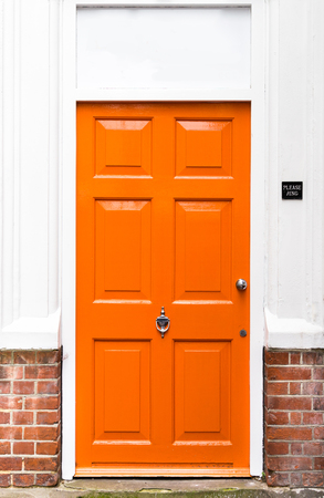 red door: Single bright orange painted wooden door with red brickwork and white walls