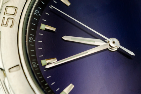 hands  hour: Macro closeup of a silver watch face with hour second and minute hands visible upon a blue metallic surface