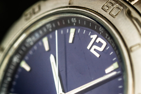 tachymeter: Macro closeup of a silver watch face with hour second and minute hands visible upon a blue metallic surface