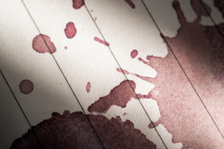 red wine stain: Closeup Macro image of a red wine stain on a pad of clean lined paper