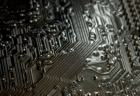 computer terminals: Macro closeup of a computer PCB Motherboard using brown and black colors with silver soldered terminals