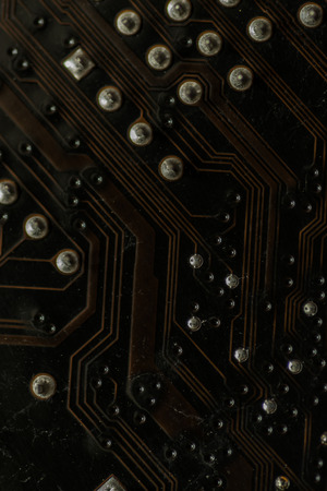 soldered: Macro closeup of a computer PCB Motherboard using brown and black colors with silver soldered terminals