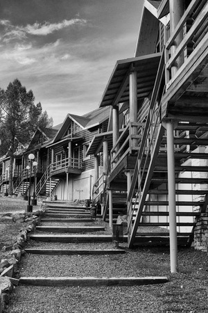 no snow: Row of empty ski bungalows with no snow and nobody in black and white