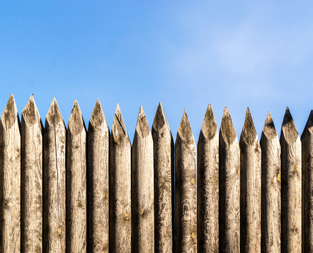 palisade: Rustic wooden palisade fencing forming a defensive barrier against a blue sky background