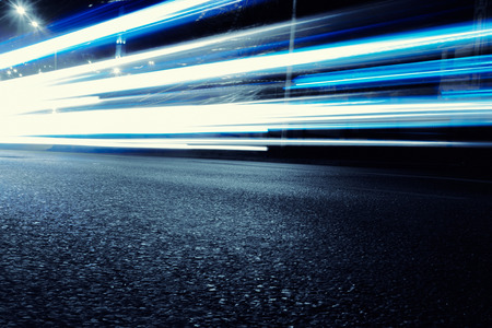 light speed: Cars create light blue light trails from their headlights as they move in a city during nightime