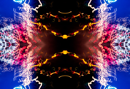light streaks: Neon lights form an abstract light painting image as they merge and collide against a black void like background, Multicolored light streaks of red, yellow, white, and pink suck into the event horizon at the core of this lightpainted image. Stock Photo
