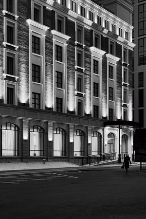 home lighting: Modern style building with night lighting shadows and highlights - a single lone woman walks into negative space on her way home Stock Photo