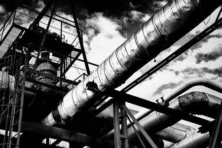 Metal industrial piping of a factory that carries watergasmaterials and metal walkways with a cloudy sky in black and white monochrome