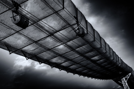 cinta transportadora: Envejecimiento cinta transportadora industrial lleva materiales de cemento más de red de seguridad de metal. Esta industria del arte abstracto de la pared con base depende de post-procesamiento pesado para crear un sentido de atención surrealista. Los fantásticos cielos azules hacen el fondo para esta pieza r