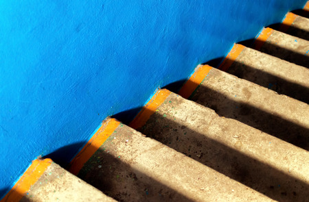 concrete steps: Blue smooth concrete and steps of aging yellow concrete creates a diagonal abstract image
