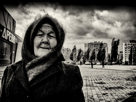 unaffected: 09102015 - An elderly woman wearing a home-knitted woollen shawl and hat with scarf stands up strongly as a fierce wind blows behind her. Men and trees in the background struggle against the howling wind, while the old woman is unaffected in Sterlitamak Editorial