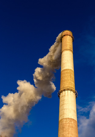 plumes: Huge red and white chimney rising high above towards a blue sky belches out vast plumes of smoke or pollution into the environment