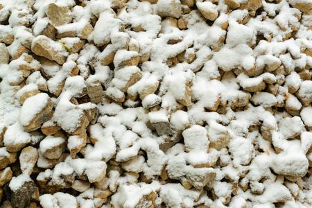 pepples: Fresh light snow falls onto many stones, suggesting a travel on construction hazard. Stock Photo