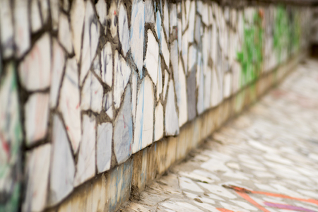 vandal: Old tiled brick wall with spray paint vandalism that cannot be read Stock Photo
