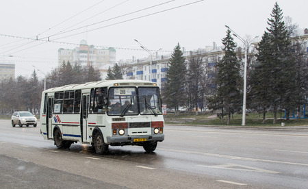 flurry: 1710 - Grey Russian bus transports people as a snow flurry marks the start of Winter in Ufa, Russia 2015