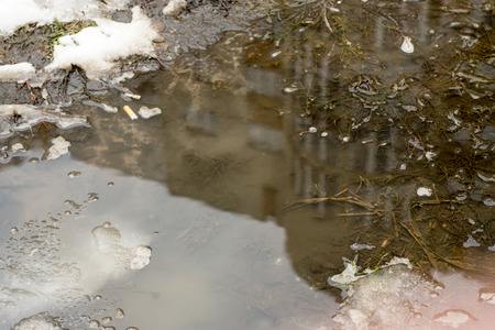 mud snow: Snowy muddy puddle reflects a tall apartment block as it gathers melted snow water Stock Photo