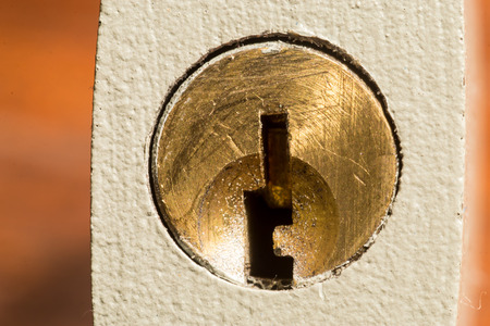 empty keyhole: Closeup of an empty keyhole lock with background and copyspace and no keys inserted