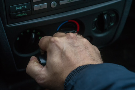 shifting: Single male hand changing gear by using an automatic gear shift in an auto car Stock Photo