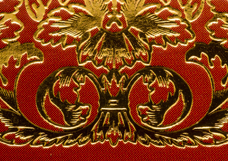 the gilding: Ornate golden gilding swirls on a brown paper or leather material