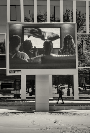 hapy: 0211 - Young woman wlaks under an outdoor television  displaying a hapy family watching a television in Ufa, Russia