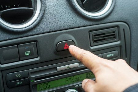 warning lights: White male hand pressing the hazard button warning lights in a car