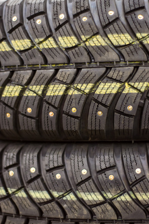 driving conditions: Row of new car snow tyres with snow spikes on display in an auto shop in preparation for winter driving conditions. Stock Photo