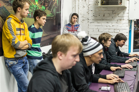 cs: UFA, RUSSIA - NOVEMBER 13, 2015: Young Russian teenagers relax by playing competitive video games as friends in a local Internet bar that specializes in online gaming and LAN parties in Ufa, Russia during November of 2015