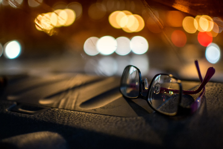 Pair of women driving glasses sitting on a car dashboard at night with defocused car headlights in the background