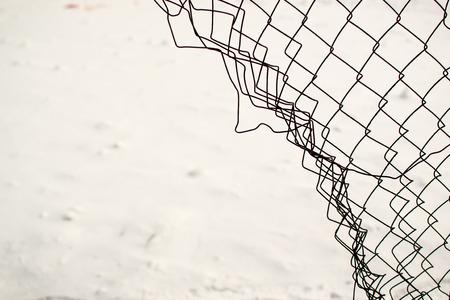 cadena rota: Broken valla de tela metálica con un fondo blanco de la nieve Foto de archivo