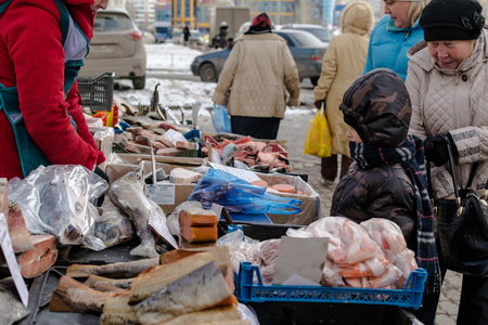 fishmonger: UFA, RUSSIA - NOVEMBER 12, 2015: Young Russian by looks at fresh fish on display at a local fishmonger stall in Ufa, Russia during November of 2015. The fish are a valuable food resource for the winter months ahead. Editorial