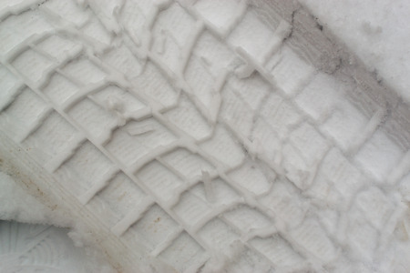 wintry weather: Car tire imprints dug into fresh winter snow during a snowstorm in the wintry weather months and icy chills making driving hazardous
