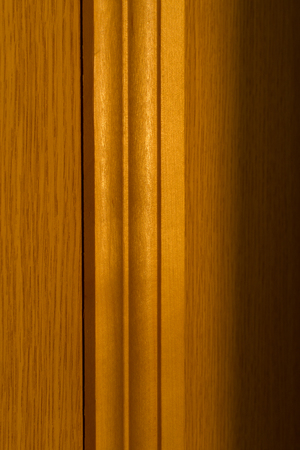 joins: Close-up image of wooden door frame with natural sunlight showing the wood texture and joins
