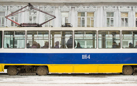electric tram: Yellow and Blue Electric Tram with a typical Russian carved window background transports people to work and study in the city of Ufa, Russia in the winter of 2015