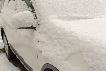 estado del tiempo: Single car covered in fresh snowfall during winter months making driving hazardous unless the vehicle is cleared of the ice and cold snow Foto de archivo