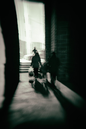 People walk though a dark alleyway with shadows and zoom lens effects creating a distorted view of the night
