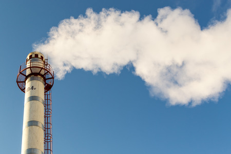 plumes: Single high industrial chimney emits long plumes of smoke and pollution into a clear crisp blue sky Stock Photo