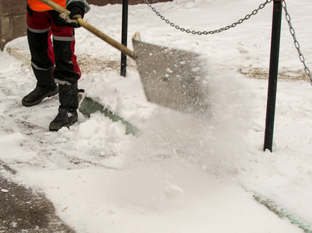 ice storm: Man wearing industrial clothing clears snow using a snow shovel Stock Photo
