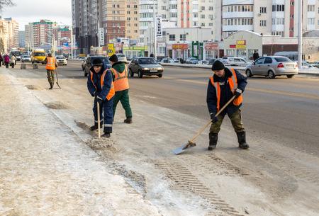 clima: 20151201 - nieve rusa equipos m�s claras trabajan en la limpieza de nieve de una calle concurrida en la ciudad de Ufa, Rusia Editorial