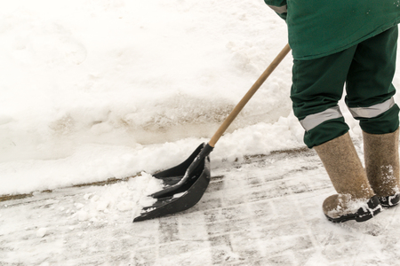 snow clearing: Street worker shovels snow clearing a path for pedestrians using the pavement Stock Photo