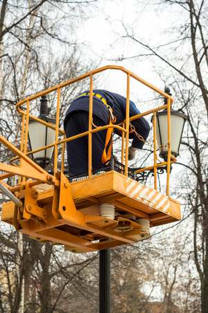 outage power: 20151210 Worker standing a mobile platform fixing an ornamental street light Stock Photo