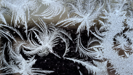 close-up of traditional winter ice crystal patterns on a clean glass background