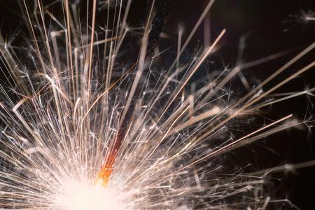sparklet: Christmas or New Year celebration close-up of a burning sparkler firework on a black background