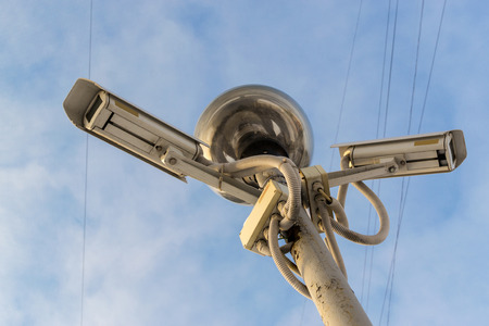 wispy: Two CCTV Cameras pointing in opposite directions with a bulb style light set against a blue sky with white wispy clouds Stock Photo