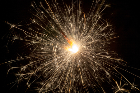 glow pyrotechnics: Christmas or New Year celebration close-up of a burning sparkler firework on a black background