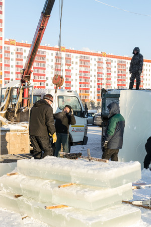 ice sculpture: UFA - RUSSIA 19TH DECEMBER 2015 - Russian Ice Sculpture workers plan and install block of ice to create winter entertainment in Ufa, Russian in December 2015