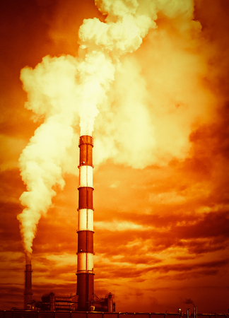 pollutants: Large industrial chimney stack emits toxic pollutants into the sky creating global warming and polluting the natural environment Stock Photo